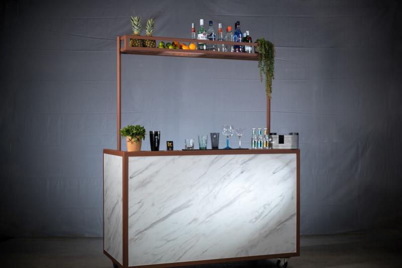 Bar van marmer en staal met cocktail glazen en flessen.