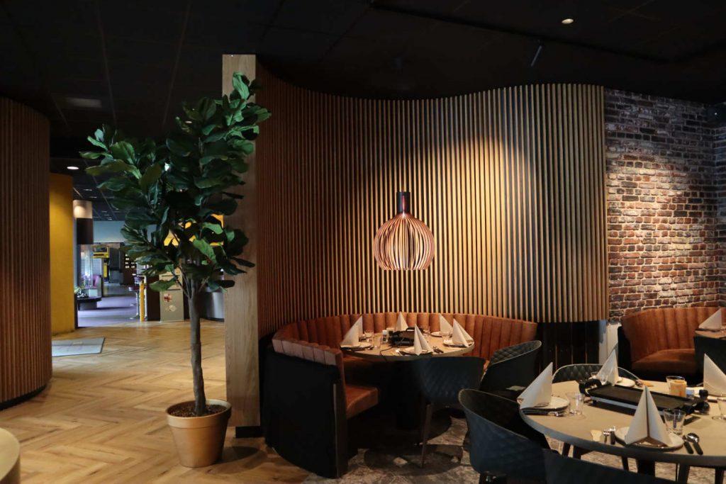 Knusse zithoek in restaurant met lamellenwand van eiken.