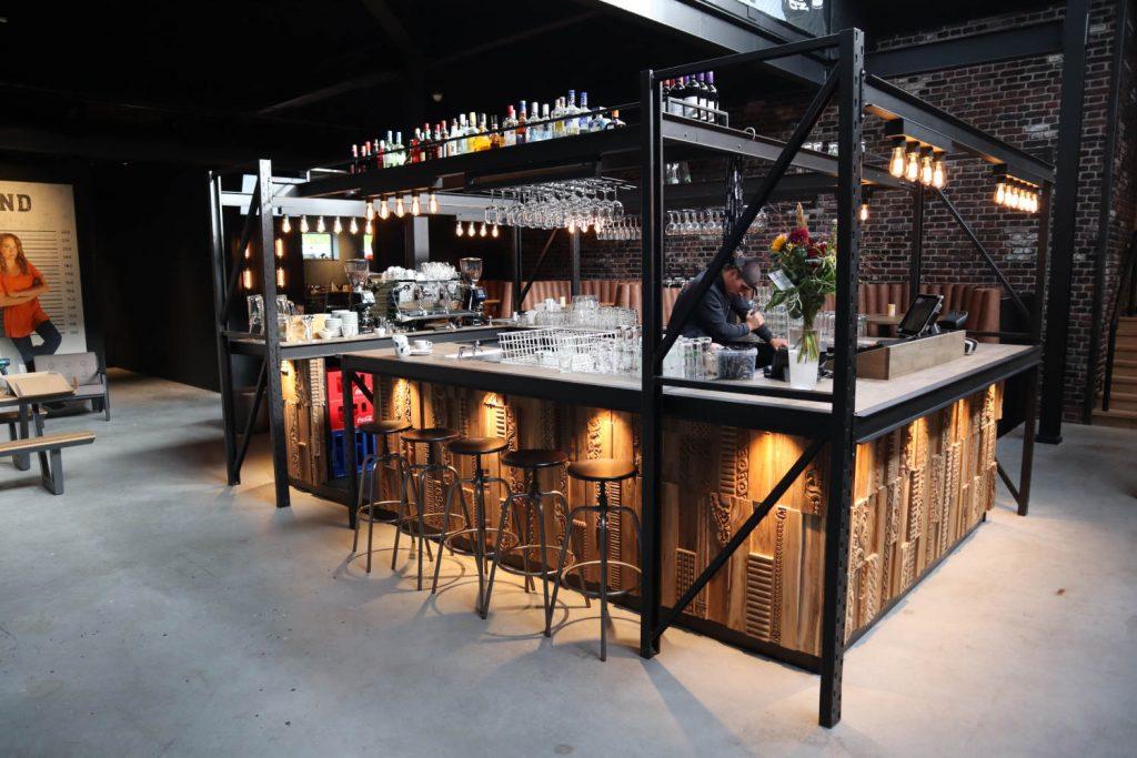 Bar van palletstelling met Wonderwall bekleding en eikenhouten barblad. Voorzien van Grolsch tapinstallatie en groot flessennest.